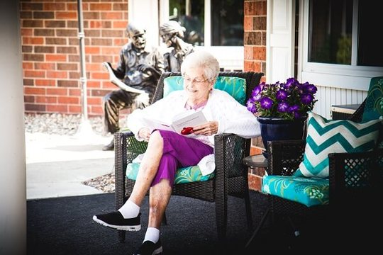 Resident sitting outside reading a book